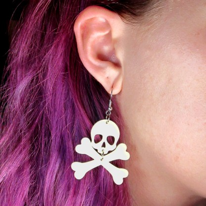 ear wearing skull and crossbones earrings to show size, purple hair