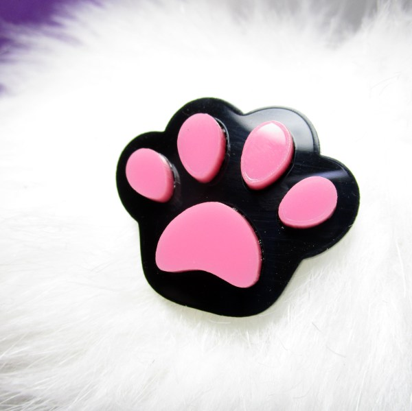 black and pink paw print brooch on white fur