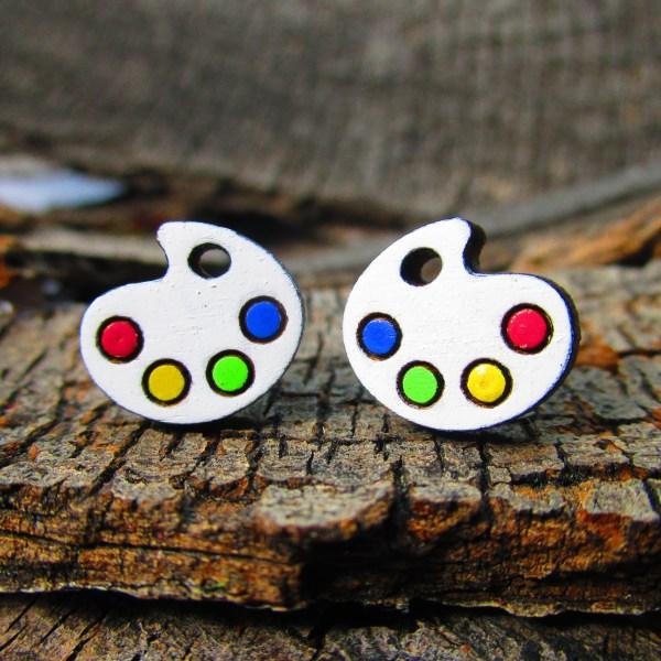 painters palette shape stud earrings on wood background