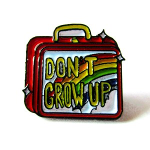rainbow lunch box shaped enamel pin that says don't grow up