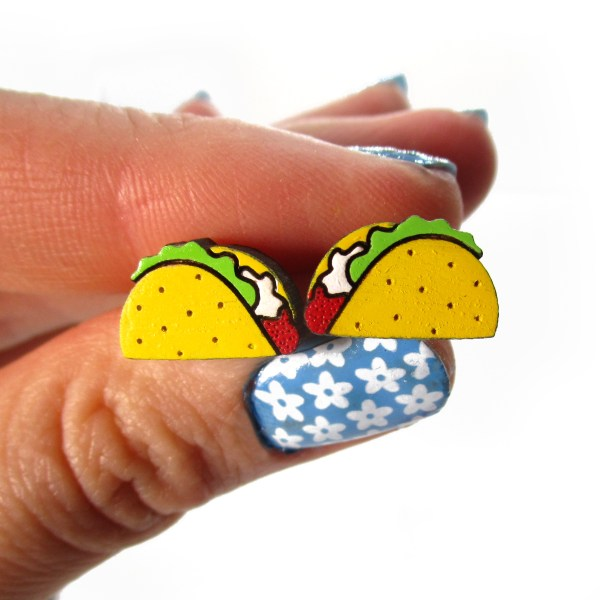 hand holding small taco stud earrings to show size