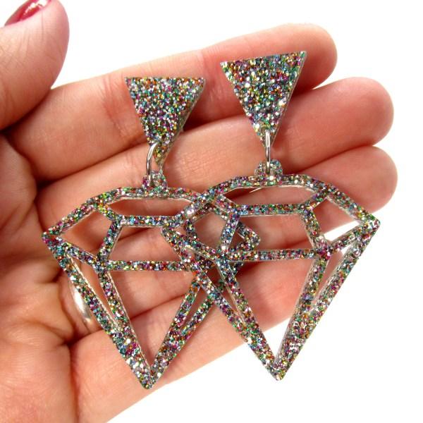geometric diamond stud earrings on hand to show size
