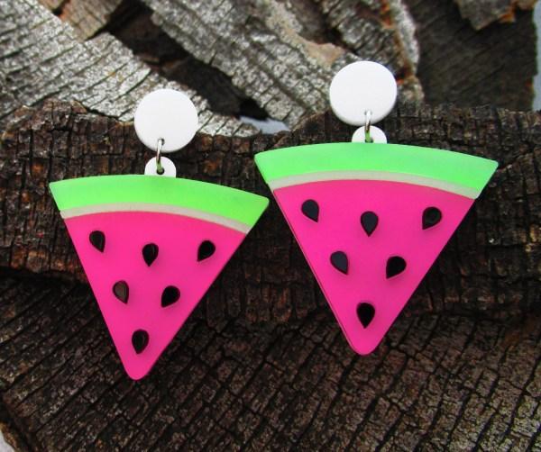 pair of watermelon seed slice stud dangle earrings on wood background