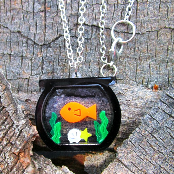 gold fish bow pendant necklace on wood background