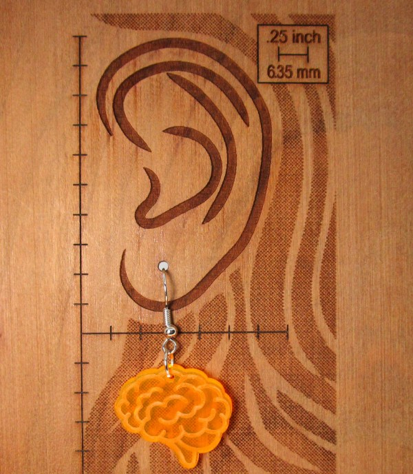 ear diagram with orange brain earring on to show size