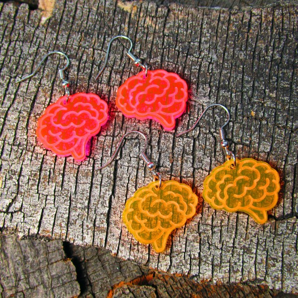 pink and orange brain shape dangle earrings on wood background