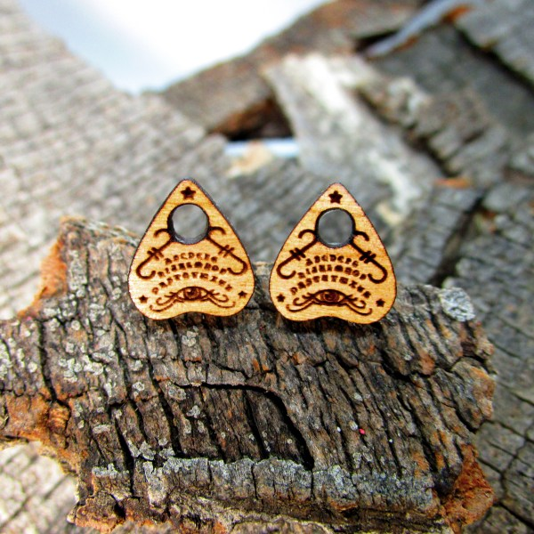ouija planchette small wood stud earrings on wood background