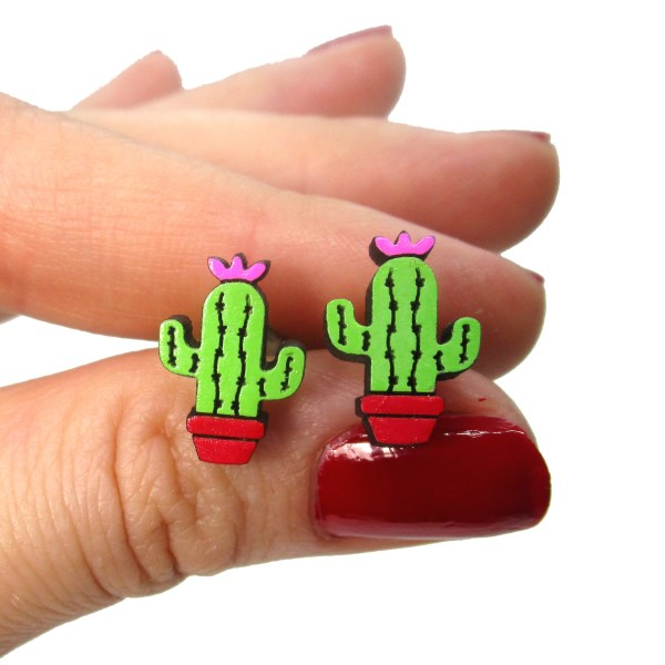 hand holding little cactus stud earrings to show size