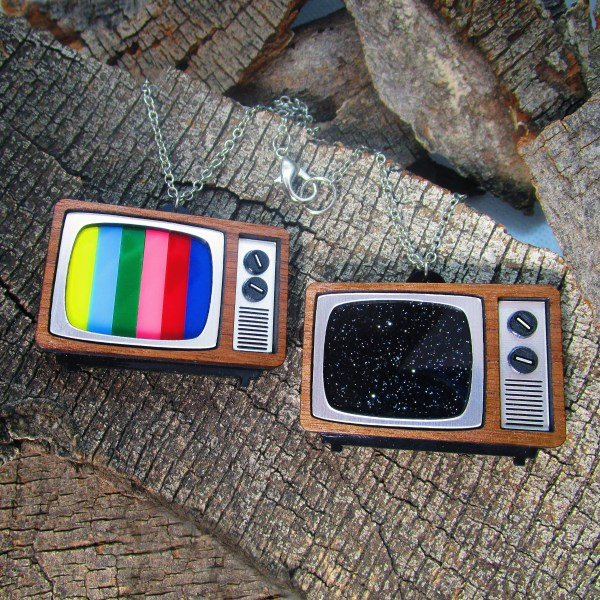 color bars and static screen retro tv pendant necklaces on wood background