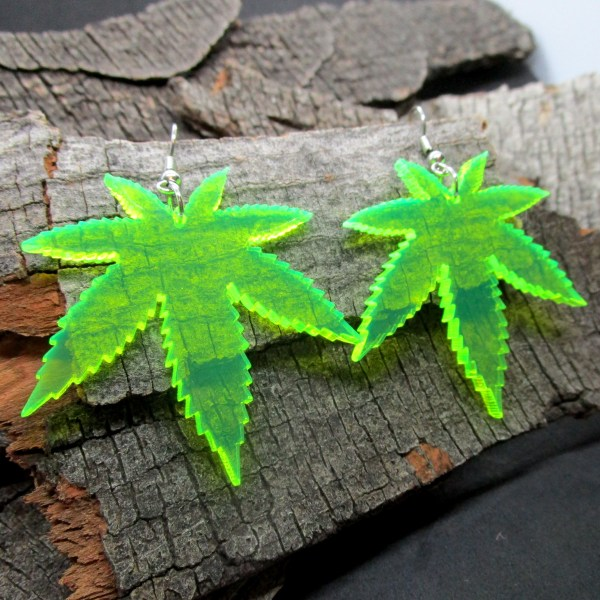 neon green marijuana leaves earrings on wood background
