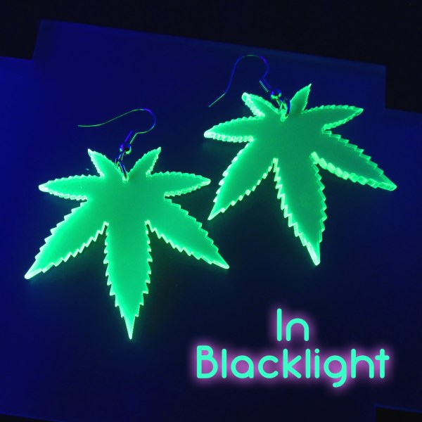 """in blacklight"" words with image showing glowing neon green pot leaves earrings"