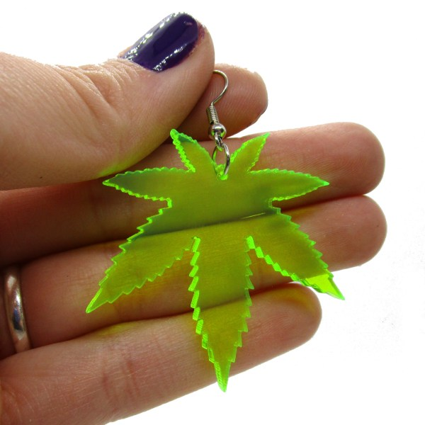 hand holding neon green pot leaf earring