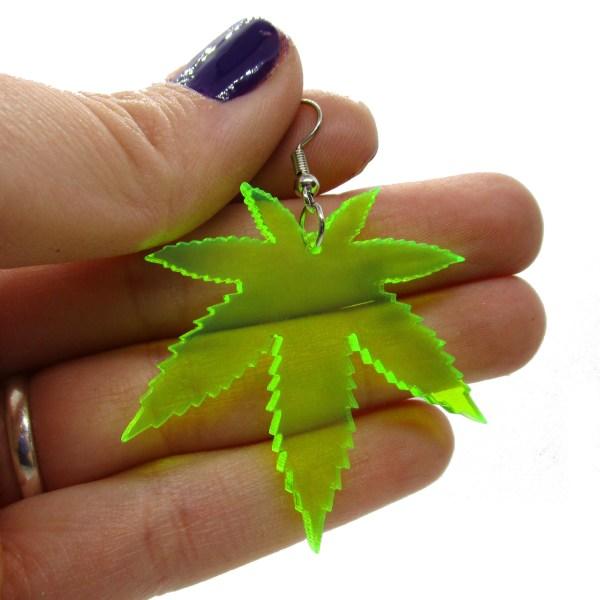 hand holding neon green pot leaf earring