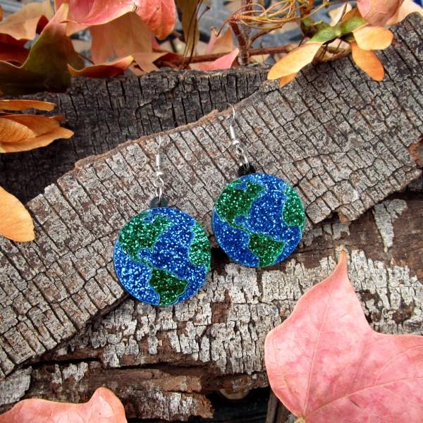 glitter earth earrings on wood background
