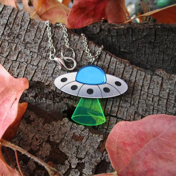 ufo acrylic necklace on bark wood background