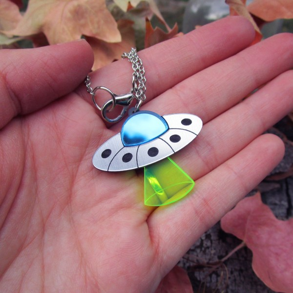 hand holding ufo alien flying saucer pendant necklace to show size