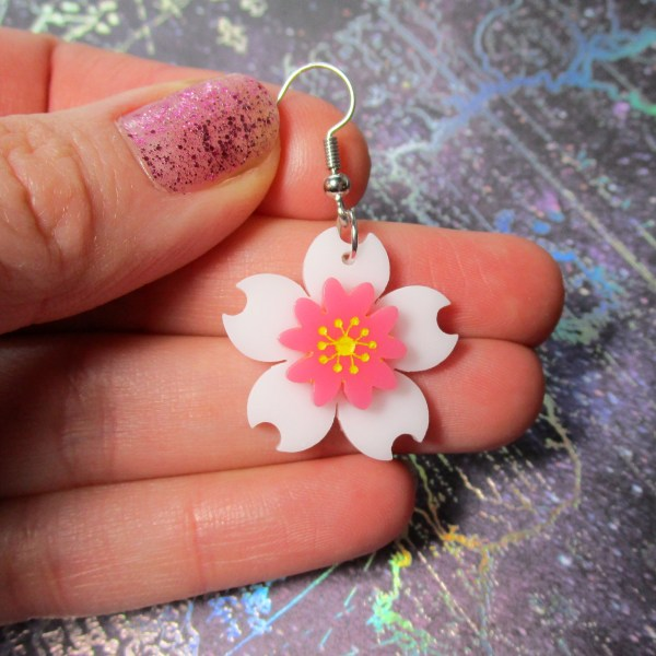 hand holding white and pink cherry blossom flower earring to show size