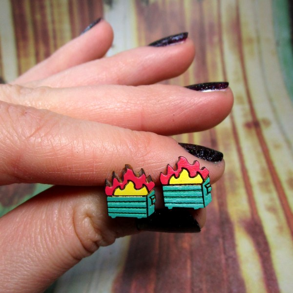 sarcastic dumpster trash fire studs held by hand to show size