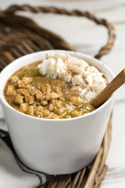 Cup of pumpkin spice chia pudding topped with walnuts, cinnamon sticks and non-dairy whipped cream
