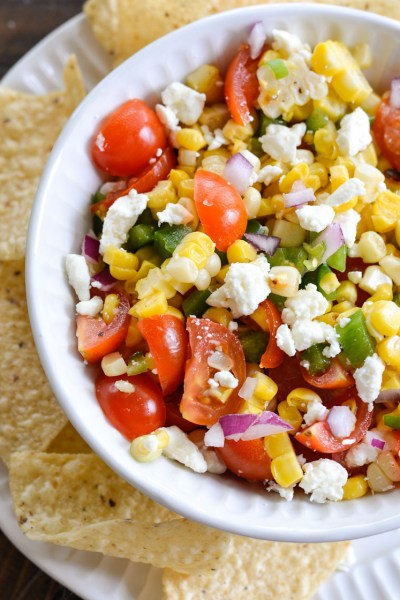 This Sweet Corn Salsa is a summer staple! Packed with grilled sweet corn, fresh tomatoes and lime juice, this is a salsa you will love on chips, tacos and wraps!