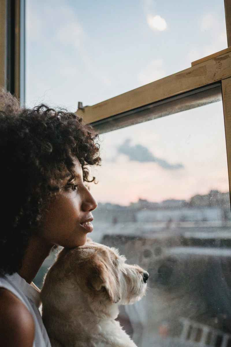 woman in black shirt looking at the window with her dog