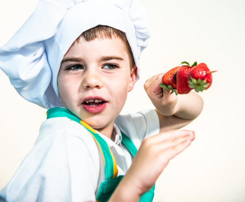 A young boy, showing off a healthy fruit skewer he has made
