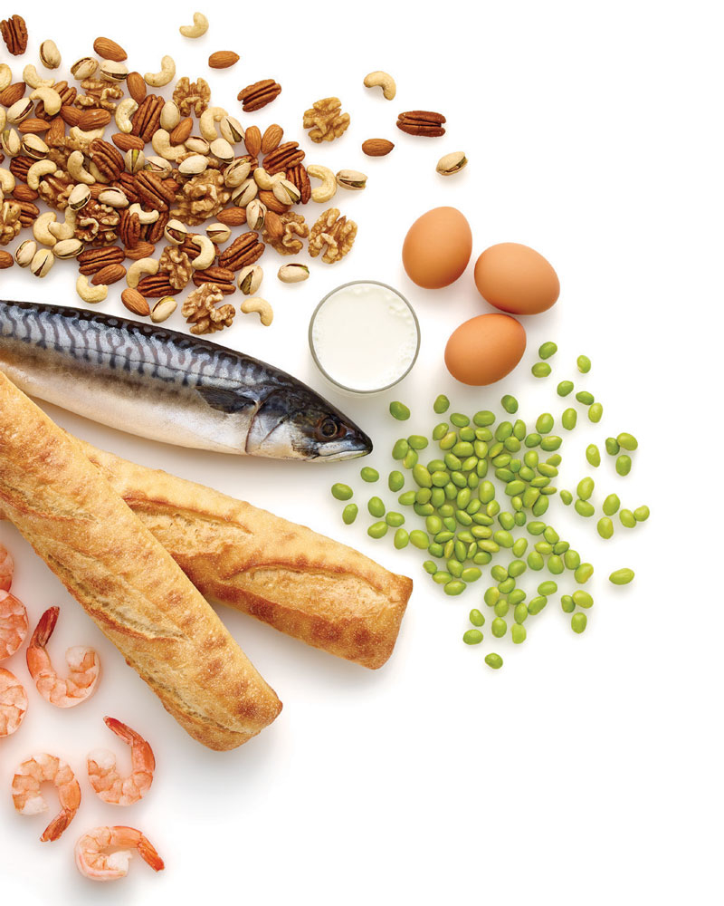 Food spread out attractively on a white table, including a fish, pulses, eggs, bread, shrimp and nuts.