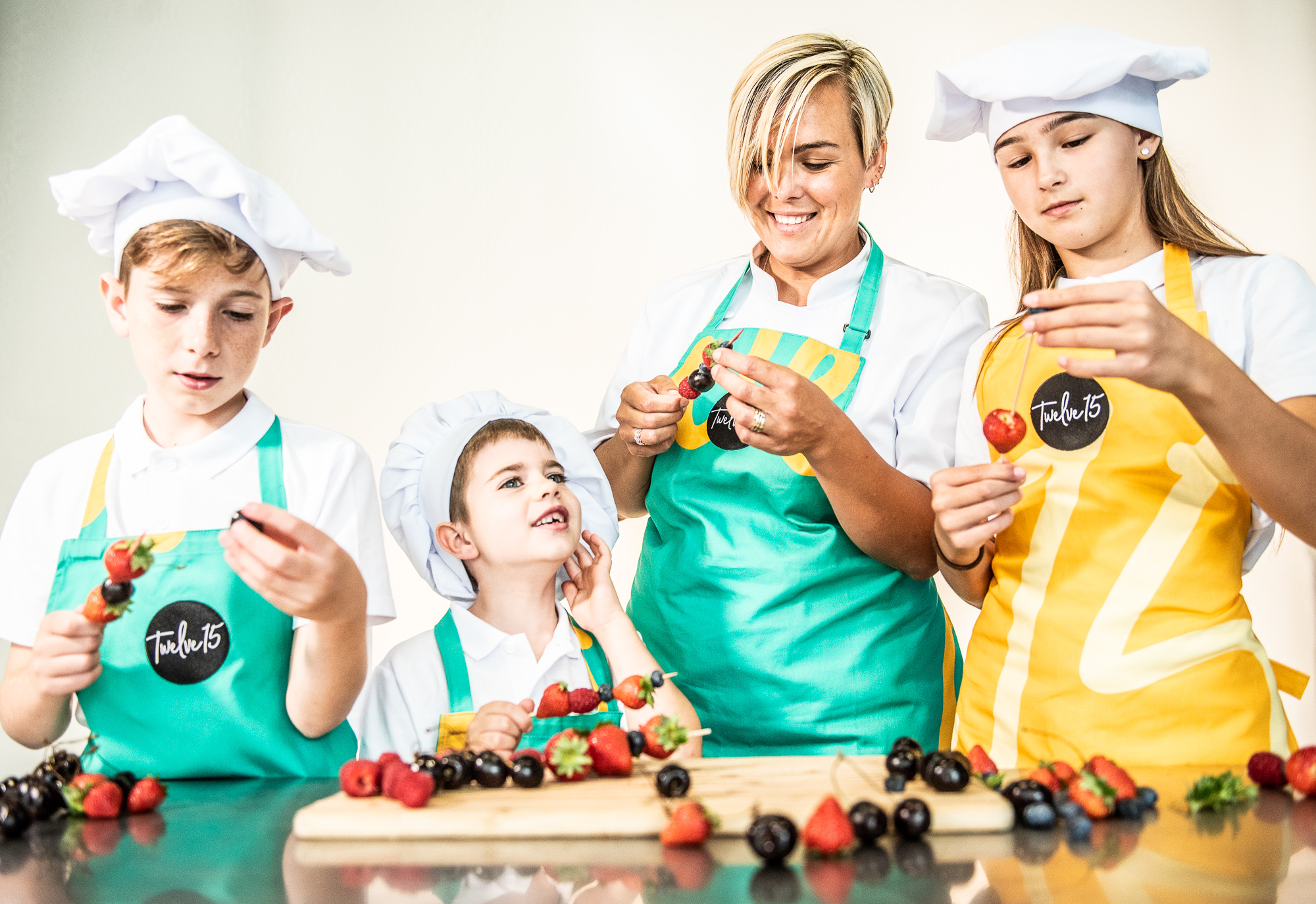 A Twelve15 staff member and three kids make healthy fruit kebabs together.