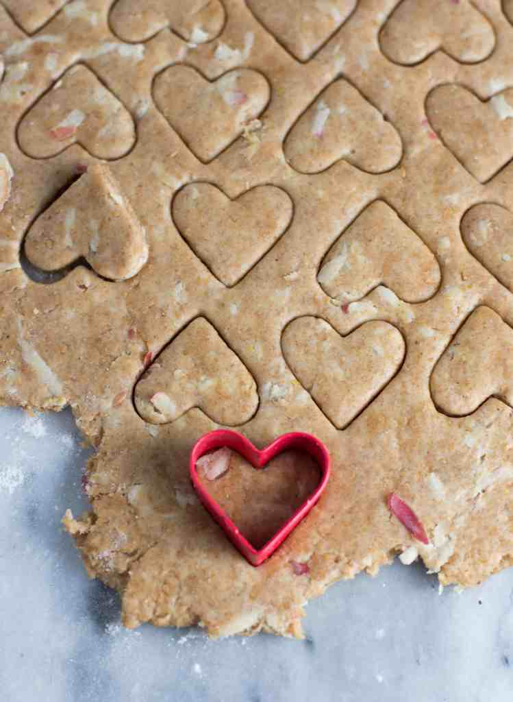 overhead shot of apple peanut butter dog treats rolled out with a heart shaped cookie cutter