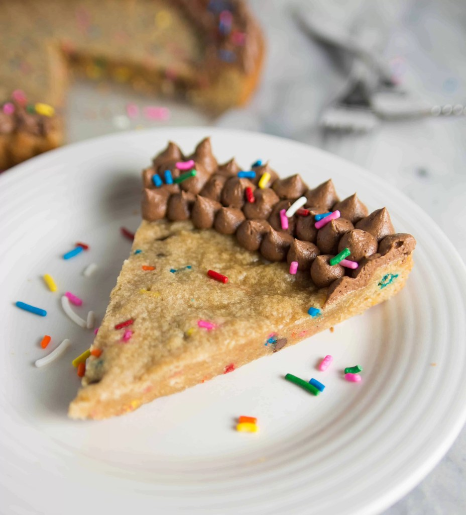 slice of funfetti peanut butter cookie cake on a plate with the cake and some forks in the background