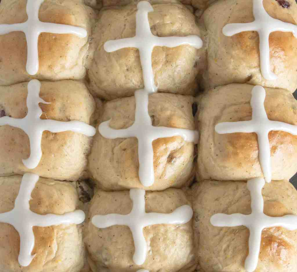 overhead shot of cranberry orange hot cross buns with frosting on top