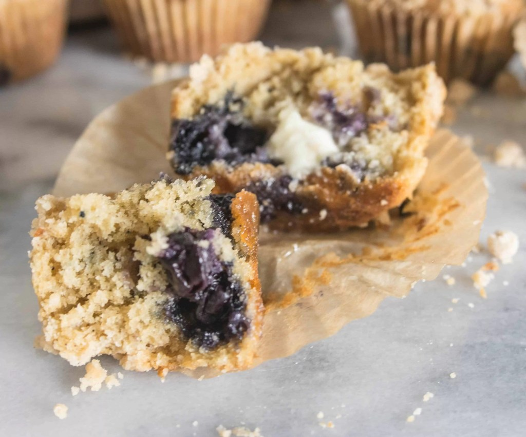 brown butter blueberry crumb muffin split open with butter melting on it