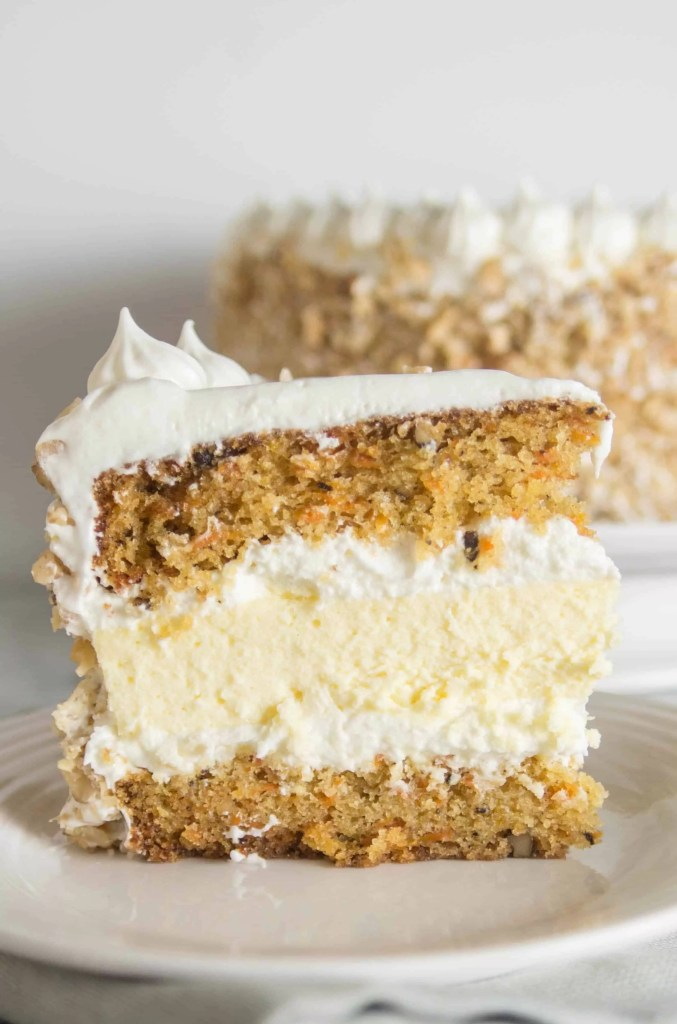 slice of carrot cake cheesecake cake sitting on a plate with the rest of the cake in the background