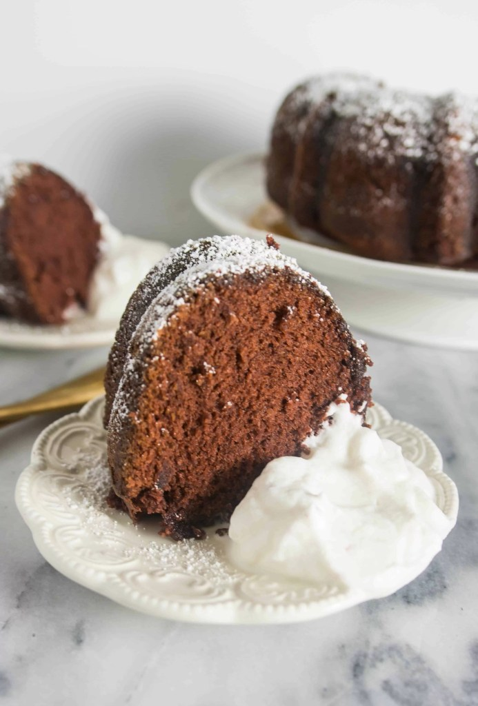 slice of kahlua bundt cake on a plate with whipped cream next to it