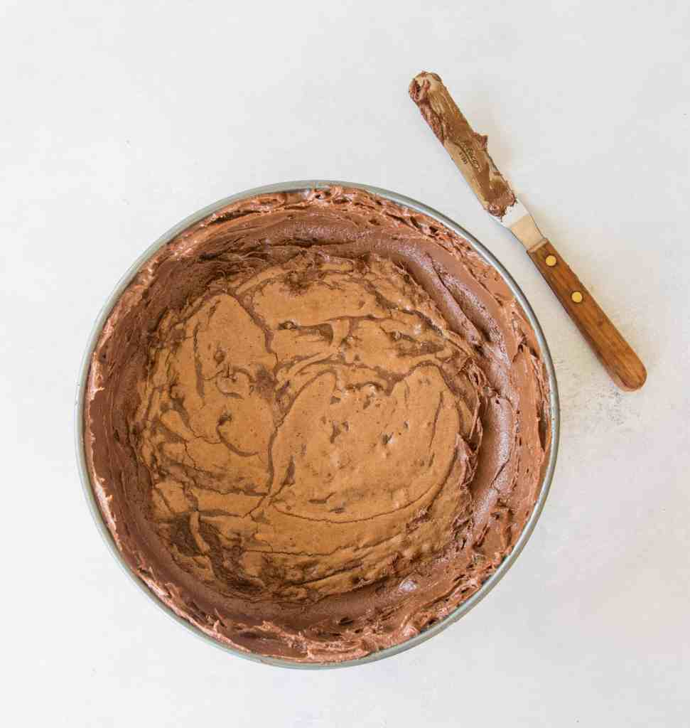 overhead image of the brownie crust spread into the springform pan before the peanut butter cheesecake filling is added