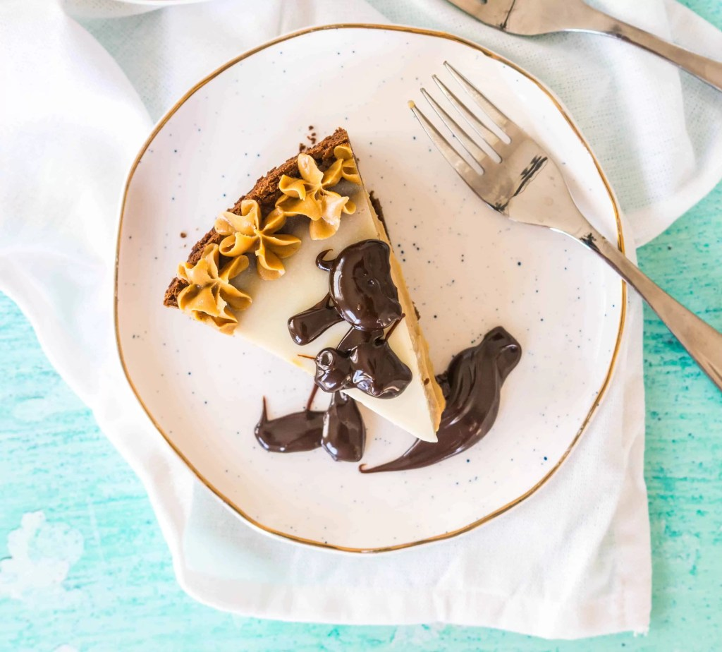 overhead photo of a slice of peanut butter cheesecake drizzled with hot fudge sauce