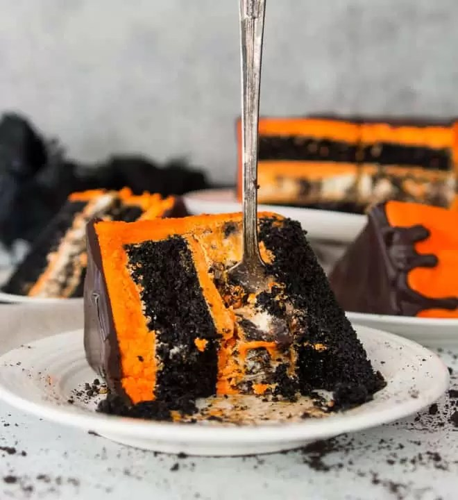 slice of black velvet cookies and cream cheesecake cake on a plate with a fork sticking out of it