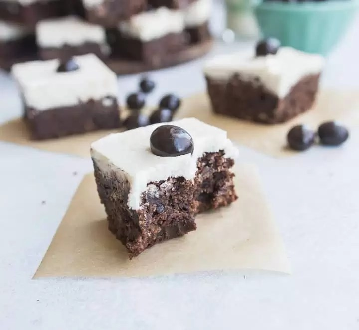 Irish cream espresso bean brownie with a bite taken out of it, sitting on a square of parchment paper