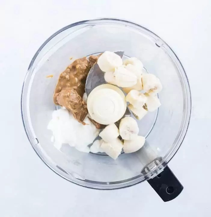 overhead shot of the ingredients for peanut butter banana ice cream for dogs in the bowl of a food processor