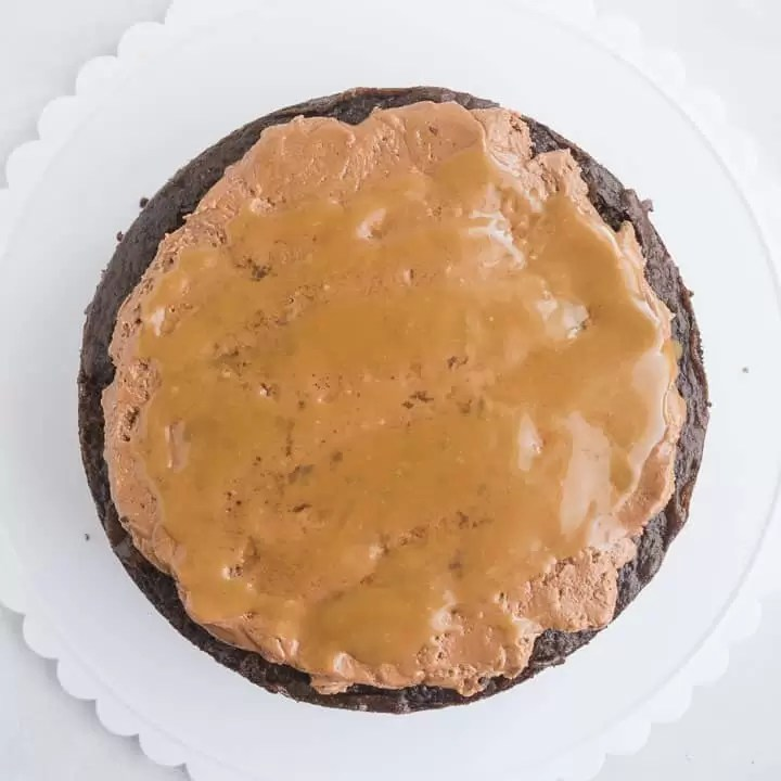 overhead shot of chocolate caramel cake (Milky Way cake) being assembled with the nougat and caramel spread over one cake layer
