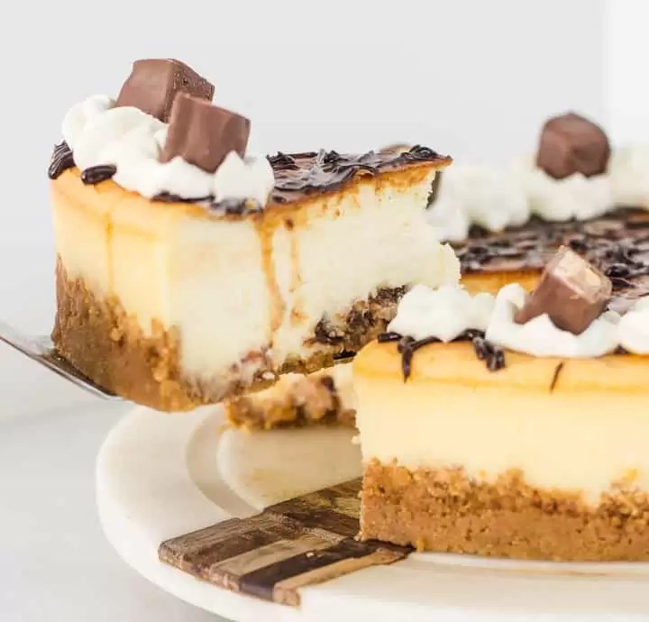 white chocolate Snickers cheesecake on a cake plate with a slice being lifted off of it
