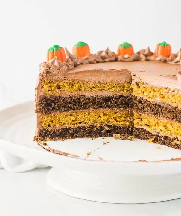 chocolate pumpkin cake on a cake stand with several slices taken out of it