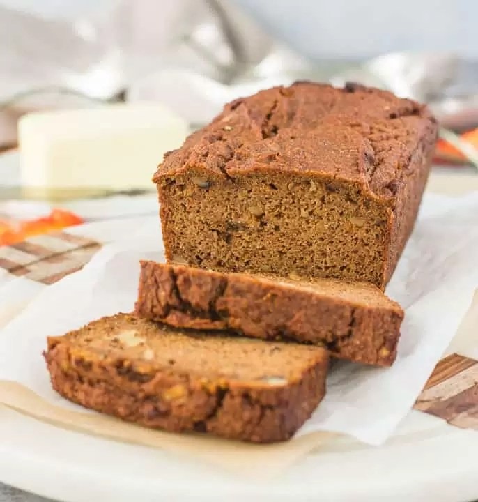 sliced paleo pumpkin bread sitting on a piece of parchment paper with butter in the background