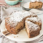sliced apple coffee cake on a cake stand with a slice of cake on a plate in the background