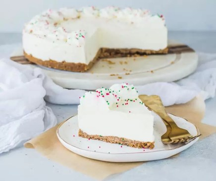 slice of eggnog cheesecake on a plate with the rest of the cake in the background