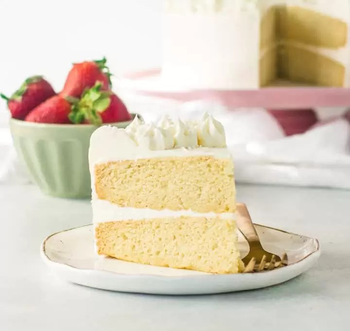 slice of white chocolate cake on a plate with the rest of the cake and a bowl of strawberries in the background