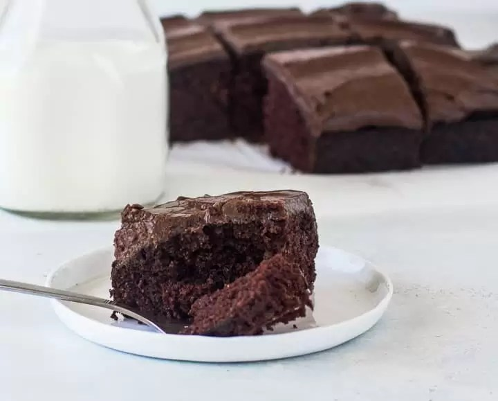 slice of chocolate dump cake on a plate in front of a bottle of milk with the rest of the cake behind it