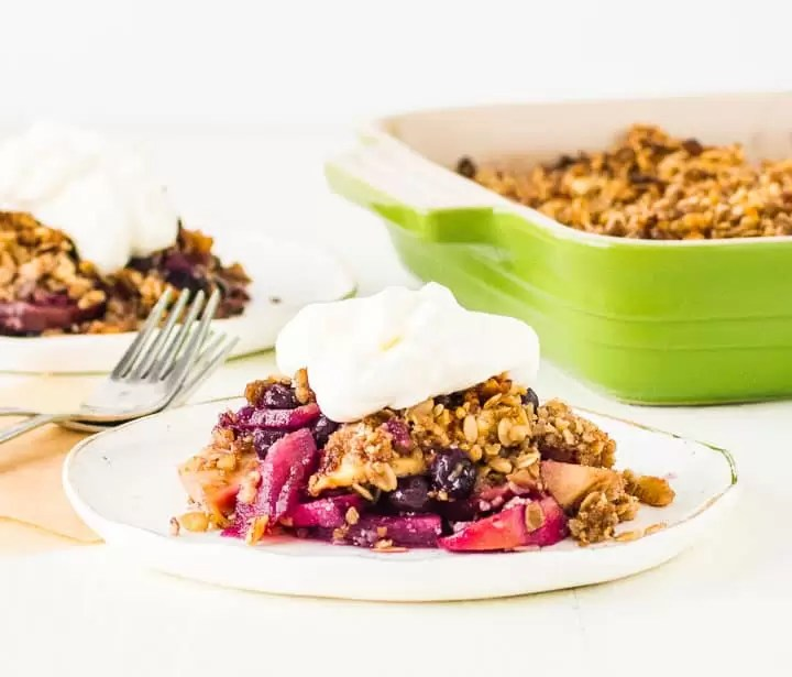 scoop of blueberry apple crisp on a plate with a dollop of whipped cream on top