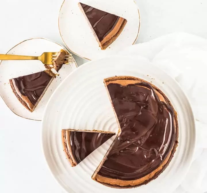 overhead photo of sliced amaretto cheesecake with two slices on plates