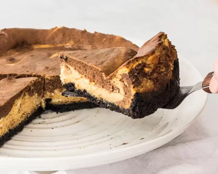 sliced pumpkin chocolate cheesecake on a cake stand with a cake server removing a slice